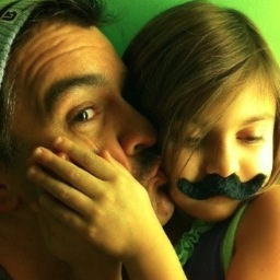 Photo of a man kissing his daughter on the cheek; daughter wearing a black fake mustache.