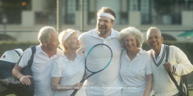 David Harbour hugs group of older people playing tennis in white shirts for Tide ad.