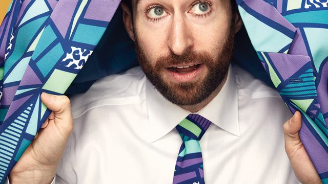 Bearded man holds a colorful blazer over his head.