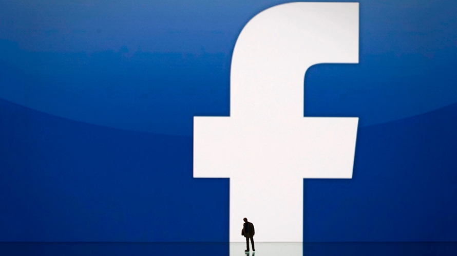 A man is standing in front of the Facebook logo.