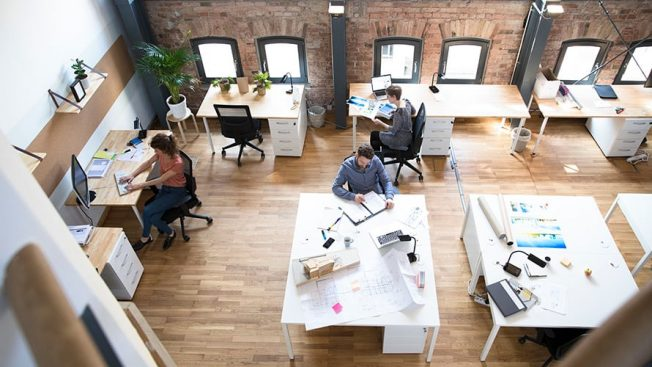 overview of an open office with desks and workers