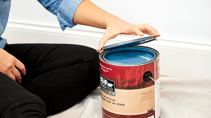 A hand lifting the top off a can of blue Behr Paint