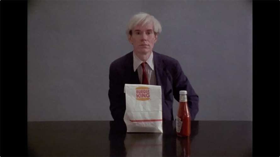 Andy Warhol is sitting at a table with a Burger King bag and Heinz ketchup.