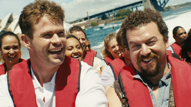 Two actors from the movie Dundee; they are on a boat wearing red life jackets