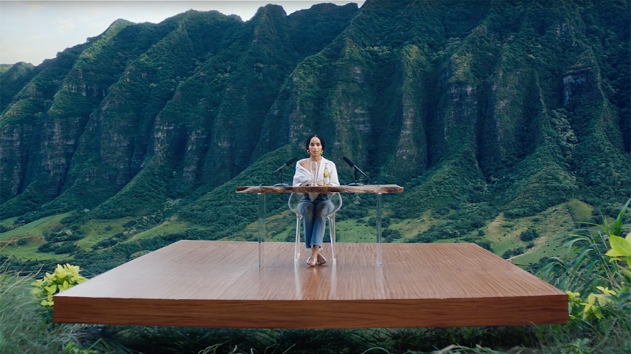 A woman is sitting on a wooden platform; there are microphones on the desk she is sitting behind; the platform is in a valley