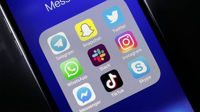 the screen of an iPhone; a folder is open revealing social media Apps like telegram, snapchat, twitter, whatsapp, slack, instagram, messenger, tiktok, and skype