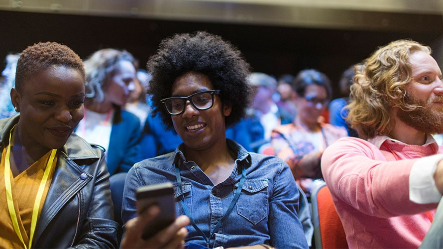 a person sits in the crowd at an event; the person in the picture is on his phone sharing something next to the attendee next to the person holding the phone