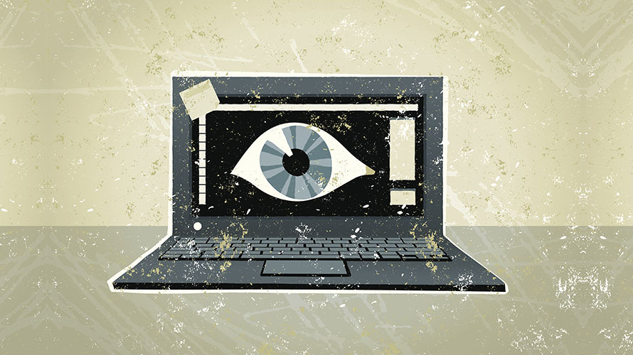 A black laptop computer; on the computer is a giant eyeball