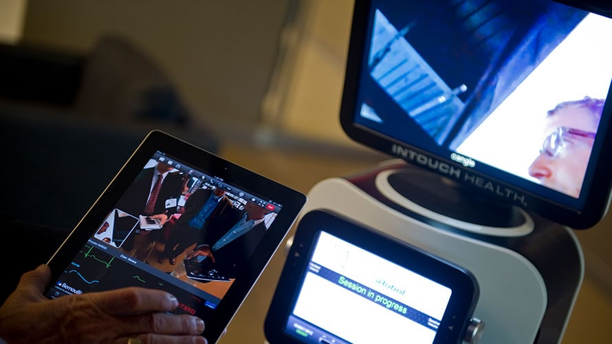 a person has their hand on the screen of an iPad; there is a second screen that shows an image of a person wearing glasses