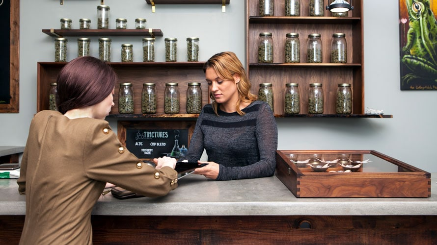 A woman is behind a herbal cannabis counter; she is helping a customer check out on an iPad