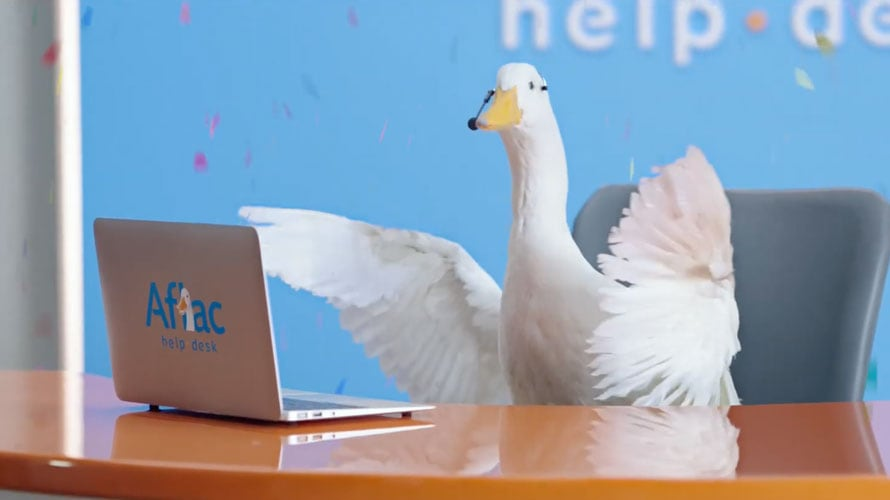 The Aflac duck is behind a computer ruffling his feathers