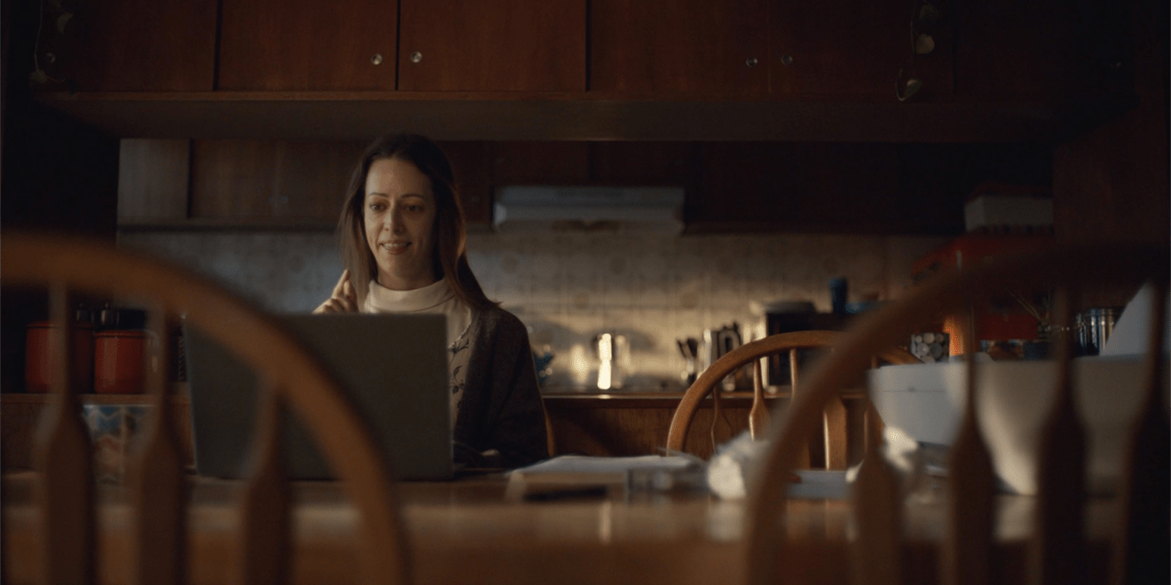 A person works on a laptop at a kitchen table.