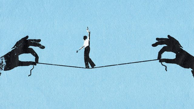 A man balances on a string; he is tight rope walking; the string is held up by two hands on each side