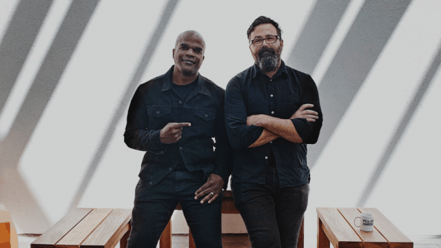Geoff Edwards and Chuck Monn pose in dark clothes for a photo against a white wall and wooden tables.