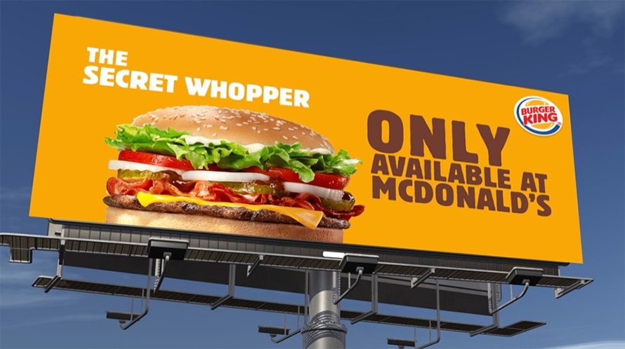 An orange billboard with a Whopper on it. The sign says 'The secret Whopper: only at McDonalds.'