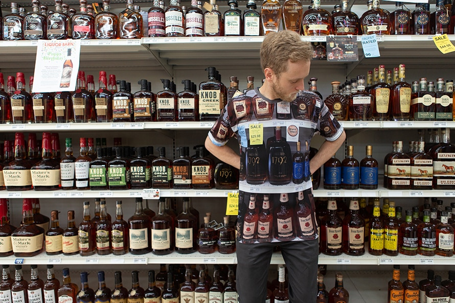 A man wearing a bourbon camouflage shirt is standing in front of a shelf of bourbon.
