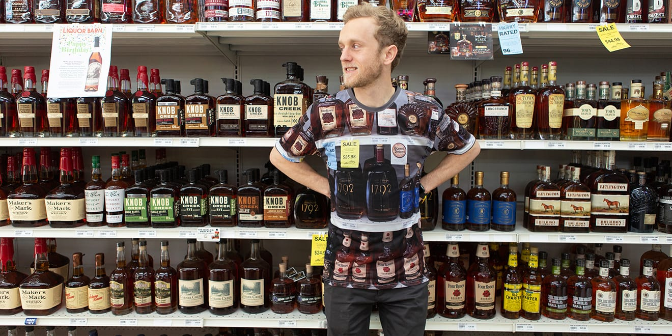 A man wearing a bourbon camouflage shirt stands in front of a shelf of bourbon.