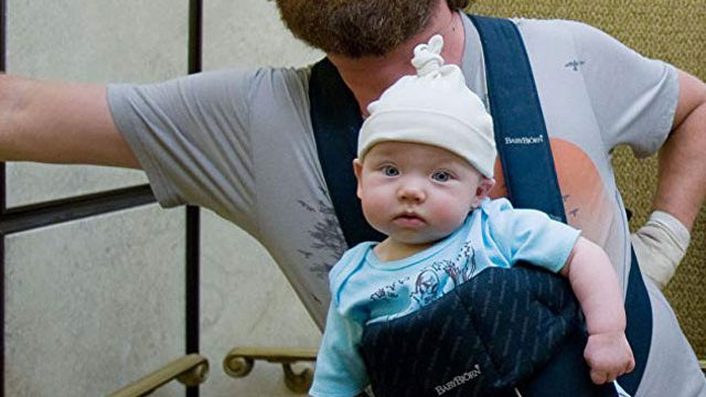 Zach Galifianakis from the Hangover is leaning against wall with Baby Carlos strapped to his chest