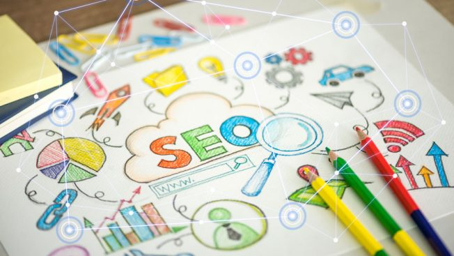 Colored pencils on a piece of paper; on the piece of paper is written SEO; Around SEO are a bunch of charts and cellular signals