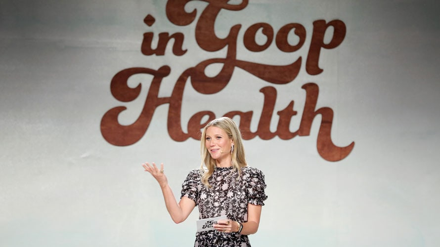 gwyneth paltrow speaks at a in Good Health event with a microphone and a notecard in her hand