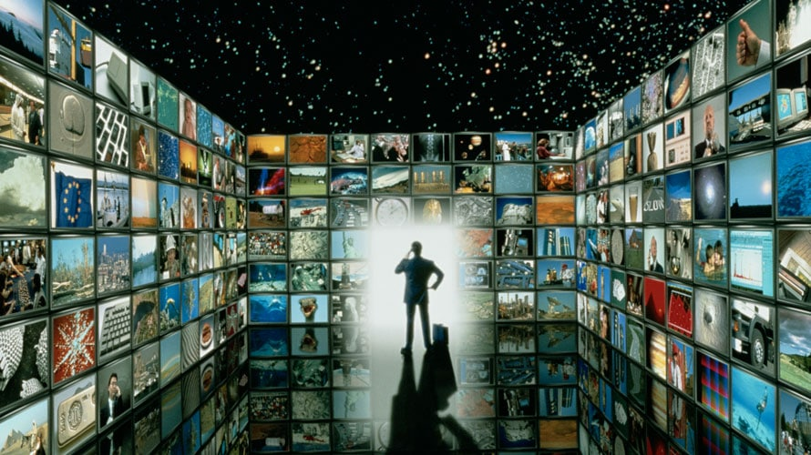 A man is standing; around him are screens on each side of him; on the massive screens there are pictures from throughout history like the moon landing