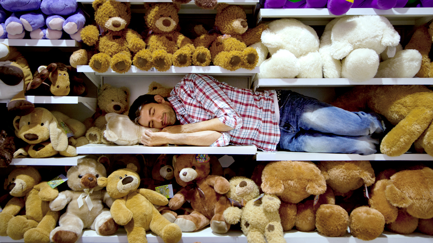 A man is sleeping on a shelf in a store amidst a bunch of stuffed animals
