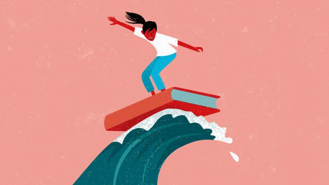 A woman stands on a book and uses it as a surfboard to ride a wave