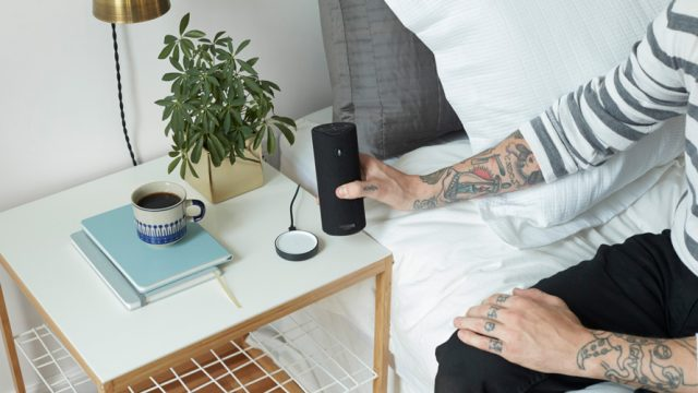 A person with tattoos on their hands and arms is seen sitting on a bed picking up the Amazon Alexa speaker