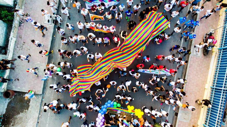 A pride community is seen carrying a rainbow flag from a bird's eye view