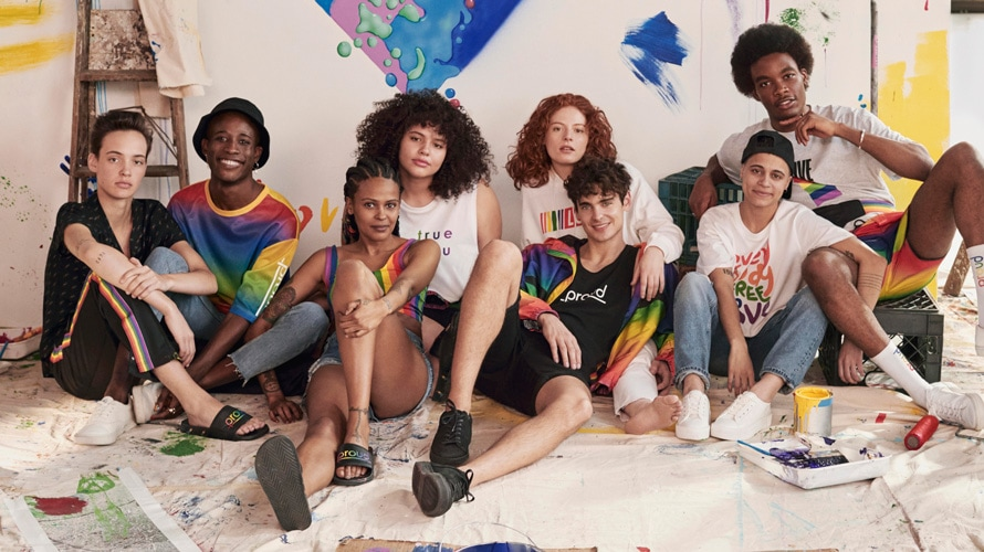 A group of young adults sit close together on the floor; many of them are wearing pride clothing
