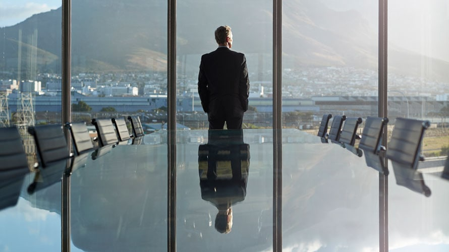 A empty conference table; at the end of the conference table is a man with his hands in his pockets looking out the window at a city