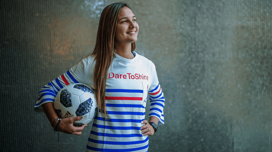 Female Soccer star poses with a soccer ball in a red, white, and blue striped shirt that says