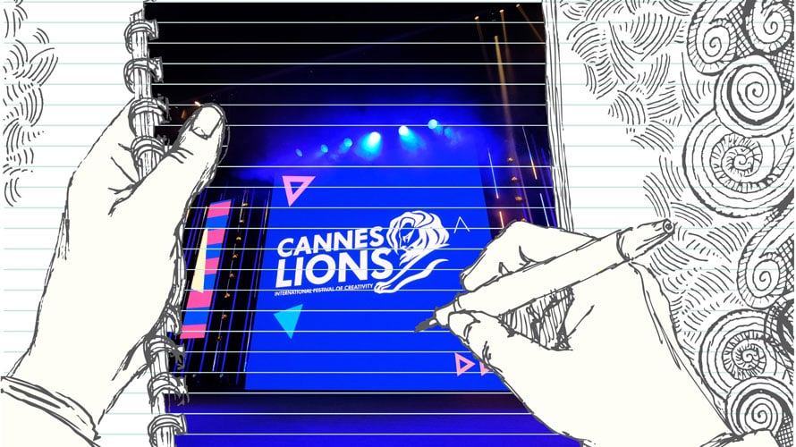 On the front of a notebook hands are seen doodling 'Cannes Lions;' in the background are various squiggly lines