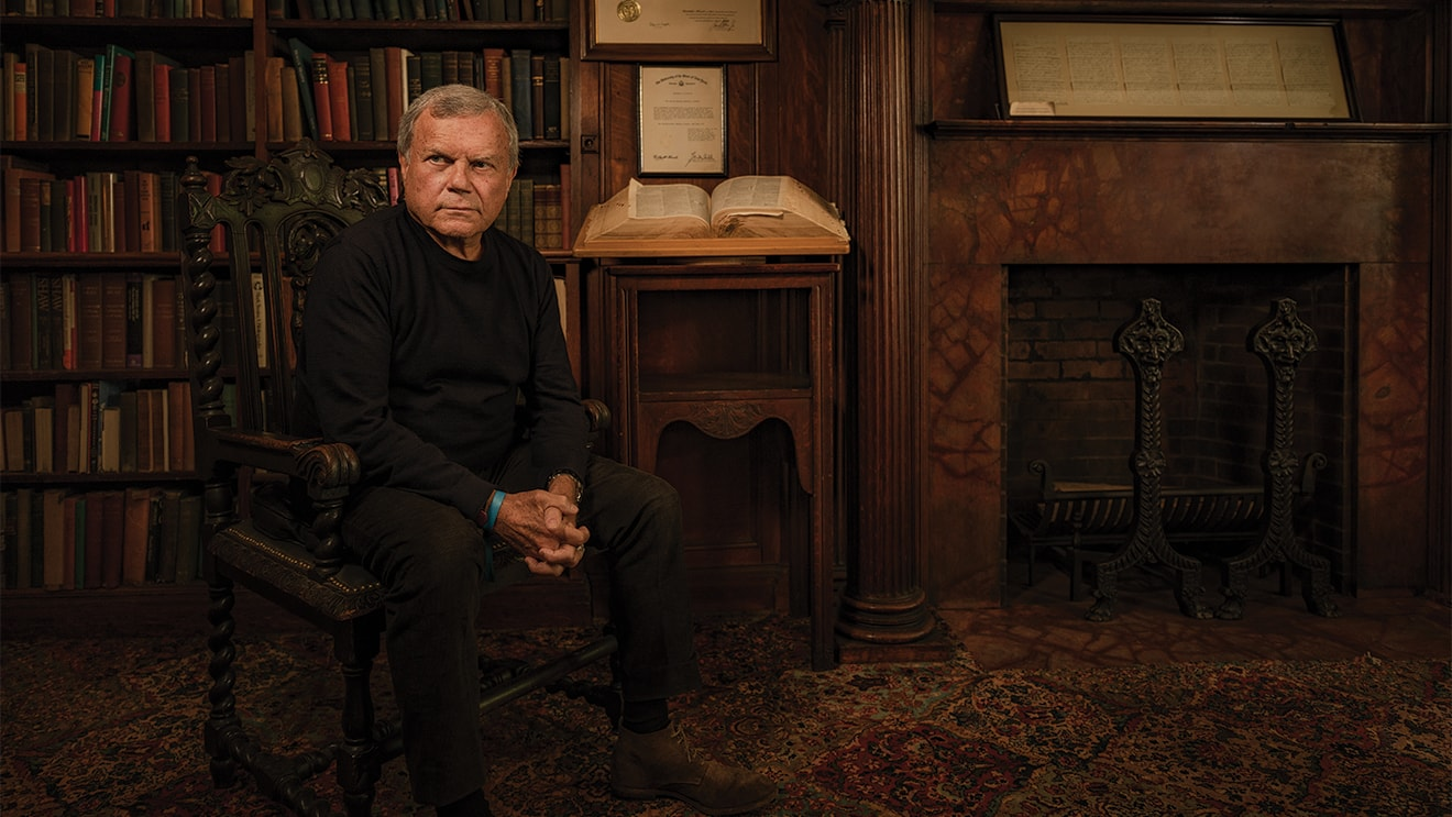 Martin Sorrell sitting in a chair in a library in front of a bookcase, a large open book and a fireplace.