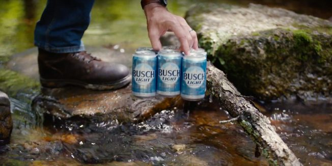 A hand reaches for a 6-pack of Busch Light beer on a rock.