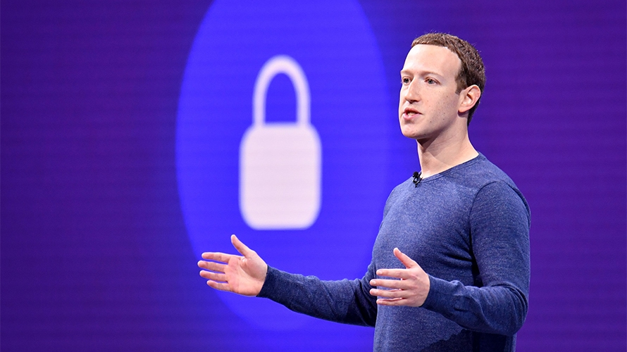 Facebook CEO Mark Zuckerberg speaks in front of an image of a lock