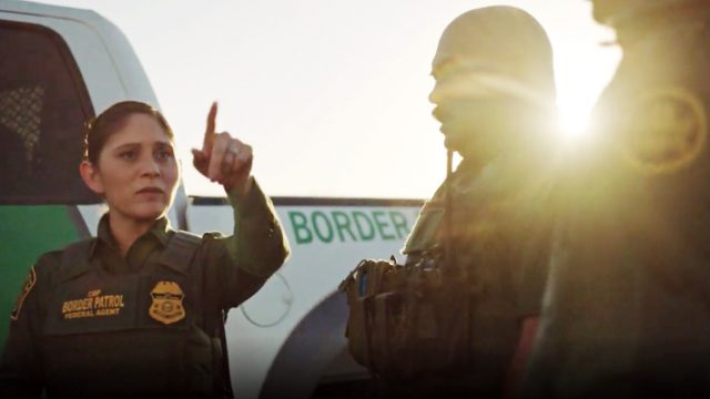 Female U.S. Customs and Border Protection agent pointing something out to her colleagues