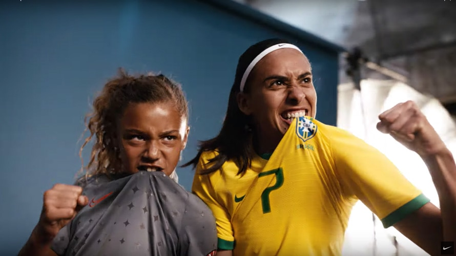 A young female soccer player and a professional female soccer player posing with fist up and biting their jerseys.