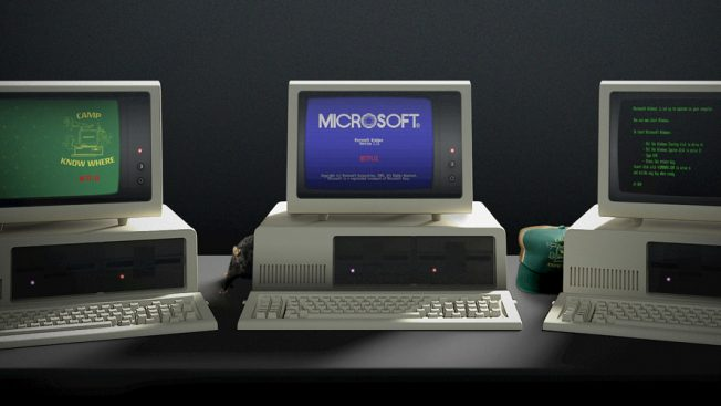 Three old Microsoft computers with Stranger Things' Camp Know Where and Netflix on the screens.