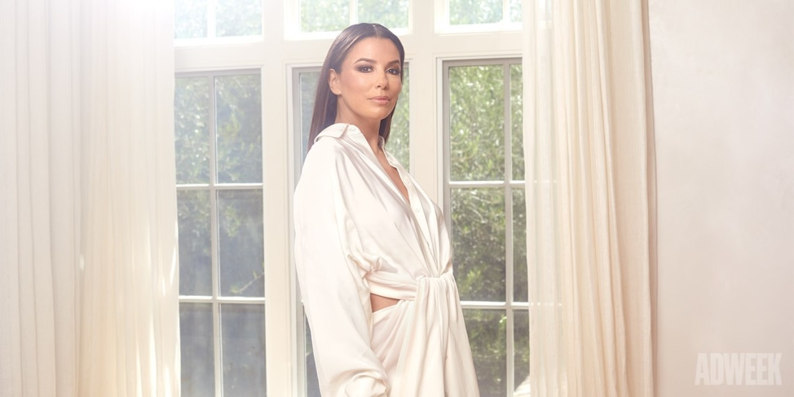 Actress eva longoria standing in a sunroom wearing a flowing white draped dress