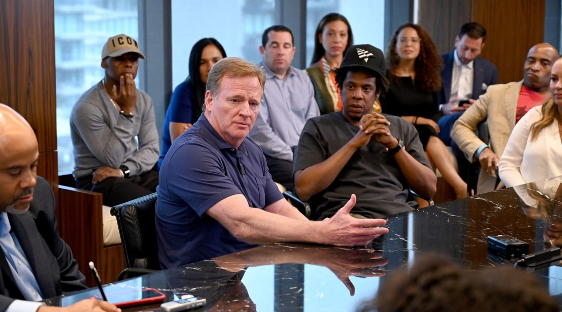 The commissioner of the NFL Roger Gooddell with Jay-Z at a conference table.
