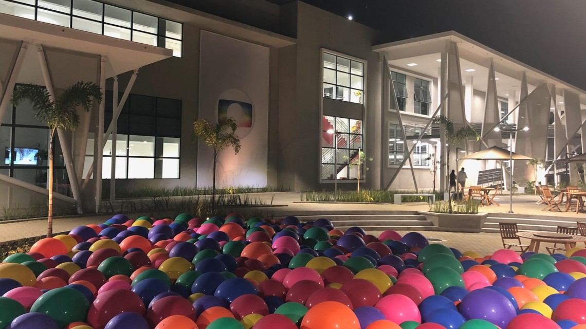 Multi-colored balloons filling a pool outside of a minimalistic mansion in Brazil hosted by Globo