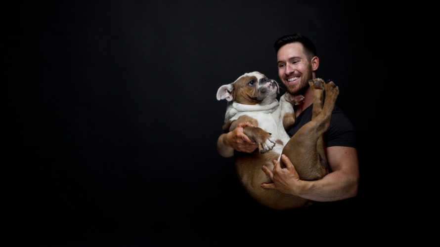 man smiling while holding a white and brown bulldog as if it were a baby