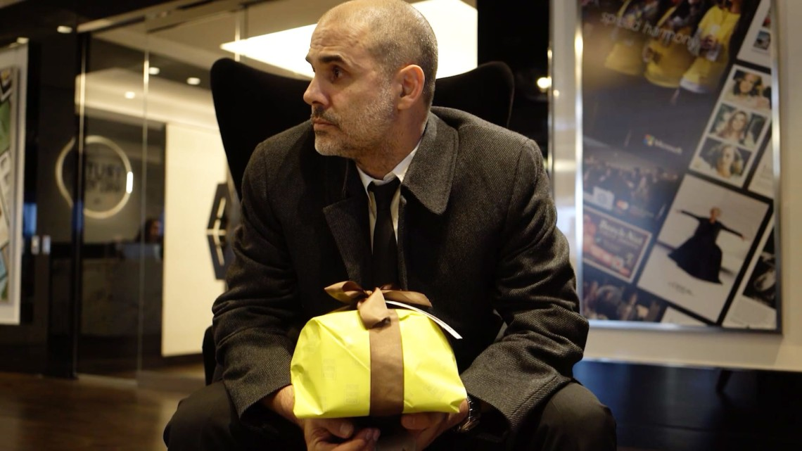 Gerry Graf wears a shirt, tie and coat and sits in a chair, holding a gift wrapped in yellow with a brown bow.