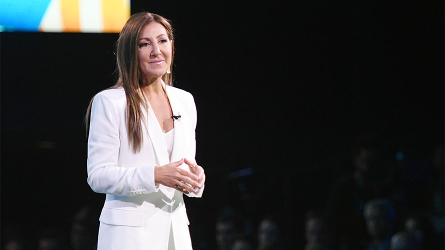 donna speciale in a white suit speaking on stage