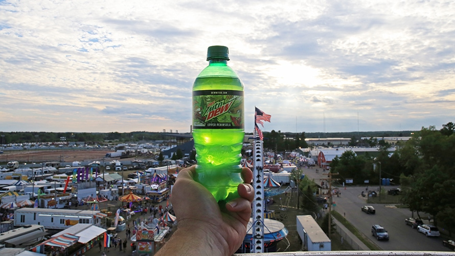 mountain dew bottle held up against a sunset near a fair