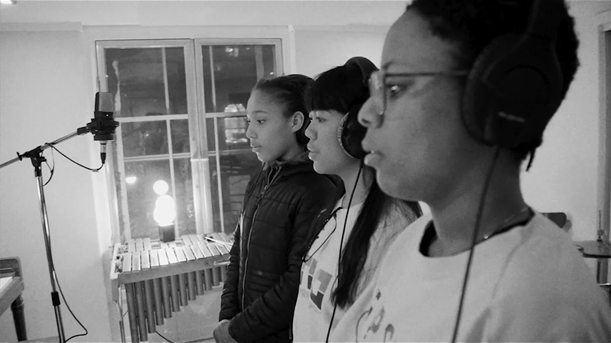 Black and white photo of three young people singing in a music studio with white walls