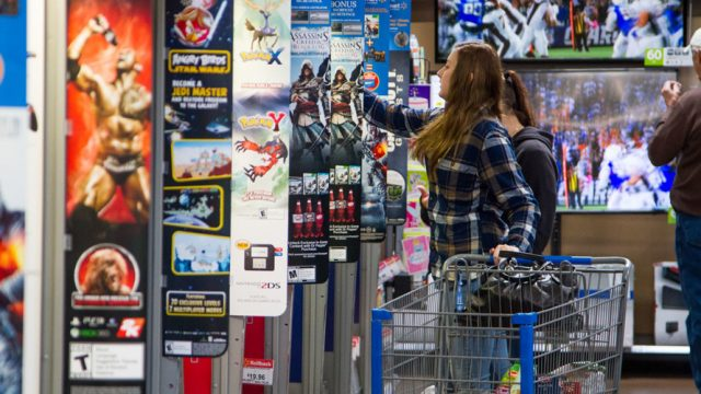 Young woman shopping at walmart's game/electronics department