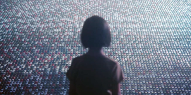 A child looks at thousands of toy cars.