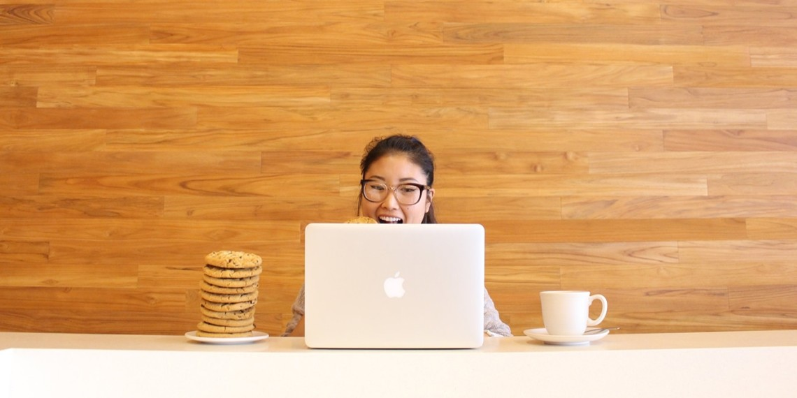 Connie Chweh sits behind an Apple laptop, with a stack of cookies and a mug.